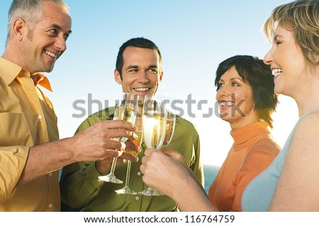 Four happy friends, or two couples, share a toast of chilled champagne at the seaside as they raise their glasses to catch the sun
