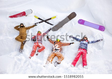 Four happy friends skiers and snowboarders are having fun and lying on snow with ski and snowboards. Aerial view #1518982055