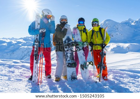 Four happy friends snowboarders and skiers are having fun on a ski slope with ski and snowboards in a sunny day and mountains view background. #1505243105