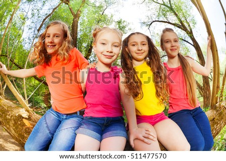 Four happy girl friends sitting on fallen tree #511477570