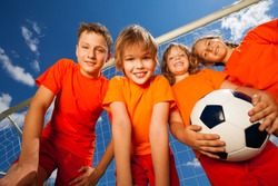 Four happy kids with football portrait