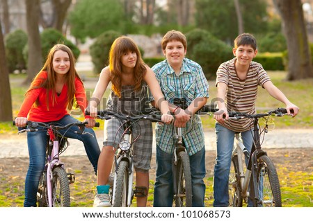 Four happy teenage friends riding bicycles in the park.