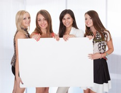 Four Happy Young Women Holding Blank Placard