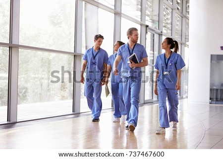 Four healthcare workers in scrubs walking in corridor