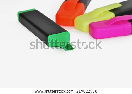 Four highlighter pens. Green, yellow, orange and pink