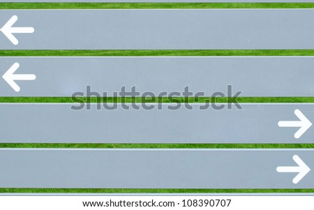Four horizontal  grey boards with white arrows pointing in opposite directions on green grass background