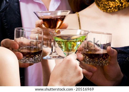 Four human hands holding the glasses of cocktails making a toast