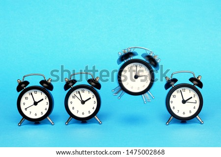 Four identical alarms on a blue background and a third alarm clock rings. #1475002868