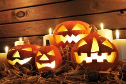 four illuminated halloween pumpkins on straw in front of old weathered wooden board in candlelight
