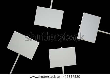 Four isolated blank signs on a black surface