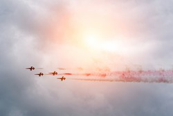 Four jets flying into the sky leaving a trail at sunset