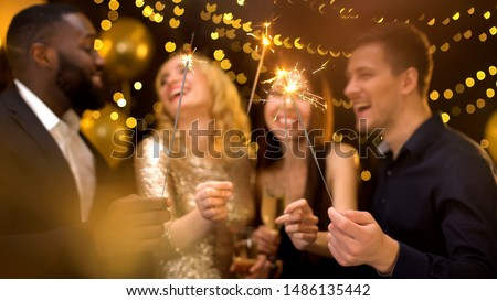 Four joyful colleagues holding burning sparklers and champagne glasses, party