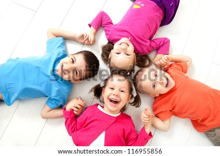 Four kids are on the floor together. Top view