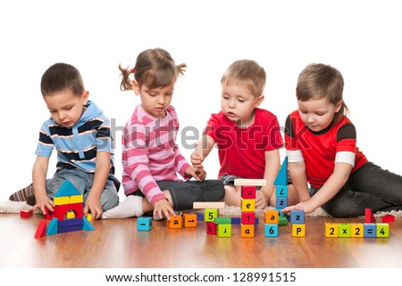 Four kids are playing on the floor with blocks