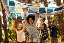 Four kids in park dancing under a picnic blanket. Group of kids having fun together in park.