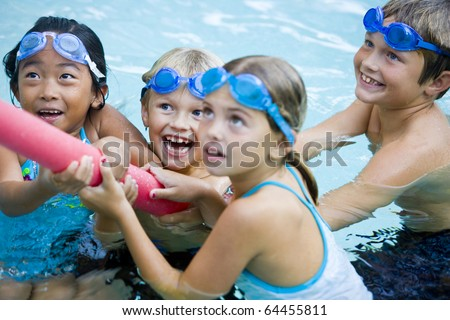 Four kids (7 to 9 years) playing tug of war with pool toy, girl in foreground not in focus
