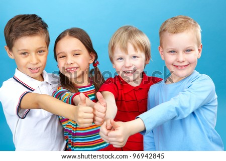 Four kids with their thumbs up looking at camera