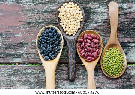 Four kinds of natural grains, consisted of black bean, red bean, green bean, and soybean seeds in wooden spoon on vintage style wooden background #608573276