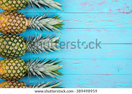 Four large ripe pineapples neatly arranged in row with copy space over wooden background in tropical theme