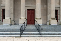 Four large round concrete columns at the top of marble steps with black iron rails to a legal building. The government building has a tall red door.  The view is from the lower corner of the steps.