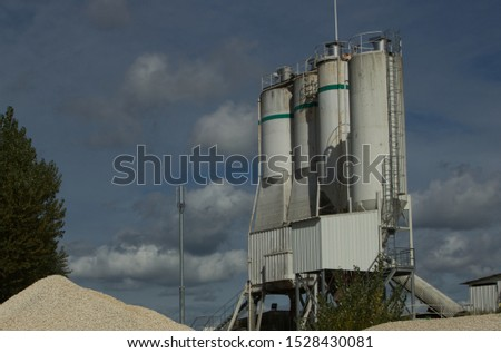 Four large silos in white with a green band at the top. Access ladders on the side. The platform is set against blue sky with some cloud, and some sand in the foreground. Cement factory.