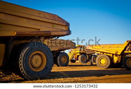 Four large yellow trucks used in modern mines and quarries for hauling industrial quantities of ore or coal. Photographed at sunset in golden light. Blackwater, Australia. Logos removed in Photoshop.