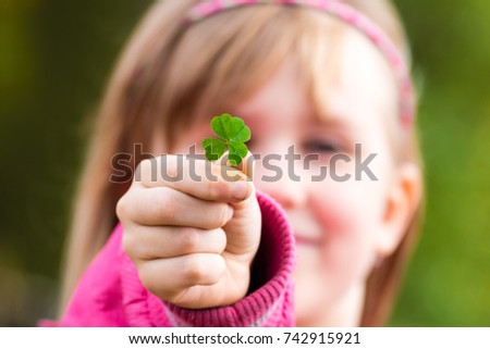 Four leaf clover in small hand of young girl in front of her face. Girl's face on background. Selective focus. #742915921