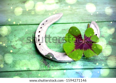 Four-leaf clover with horseshoes on a green wooden background - symbols of luck - good luck