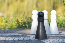 Four Life-Sized Pawns on a Chess Board, three white pawns and one black in front, focus on the black pawn
