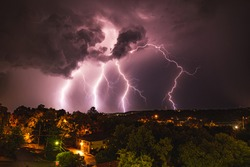 Four lightning bolts illuminate the sky above Fayetteville, Arkansas during a early summer storm