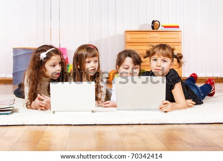 Four little friends lying on the floor with laptops