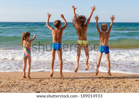 Four little kids jumping on the beach