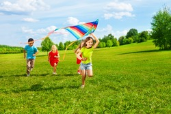 Four little kids running in the park with kite happy and smiling