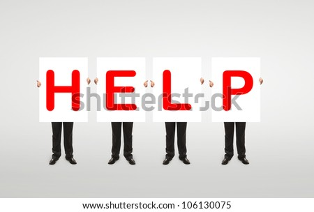 "four  man holding a white board with red ""help"" symbol"