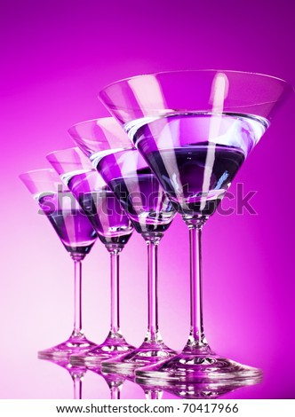 Four martini glasses on purple background