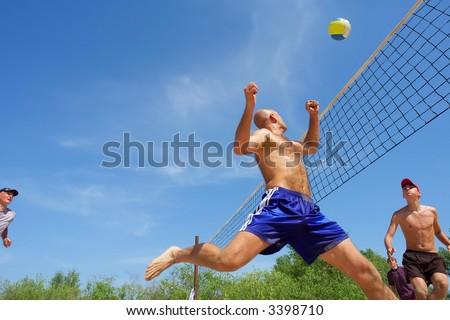 Four men playing beach volleyball - balding man runs after ball. Shot near Dnieper, Ukraine.