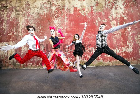 Four mimes jumping on a background of a red wall. #383285548