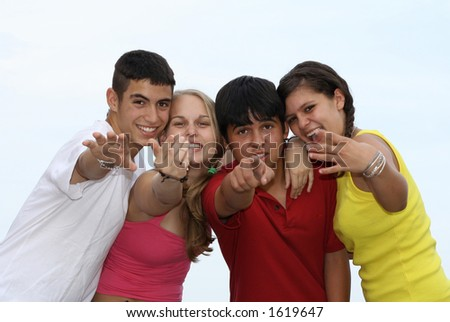 four mixed race kids beckoning to camera