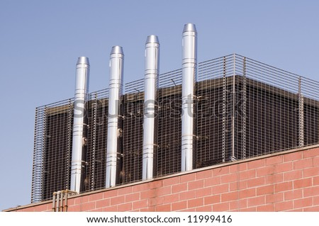 Four modern steel chimneys on a rooftop