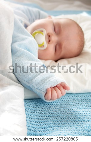 Four month old baby sleeping on blue blanket #257220805