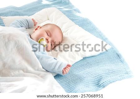 Four month old baby sleeping on blue blanket on white bavkground #257068951