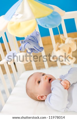 Four months old little boy playing in baby bed. Toys are officially property released.