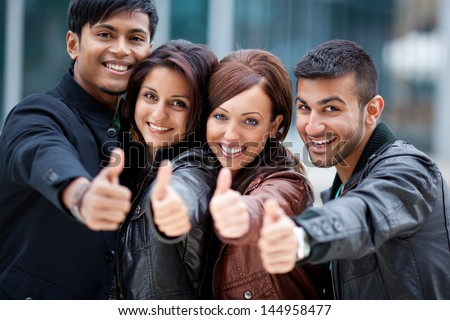Four motivated trendy young Asian friends standing close together in a row giving a thumbs up of approval and success
