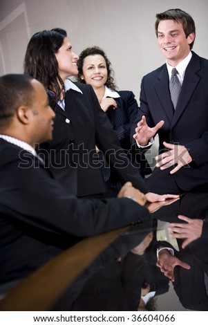 Four multi-ethnic business executives conversing in boardroom