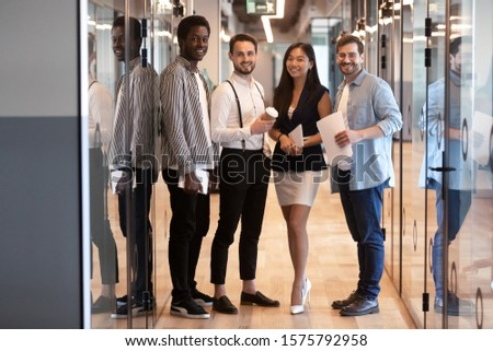 Four multi-ethnic young and confident business people international company members stands in office hallway pose for camera shooting, professionals service providers successful employees team concept