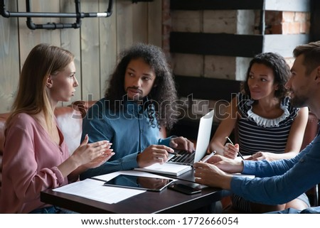 Four multi ethnic young group of employees during lunch in cafe working together on common project, corporate task, preparing for conference activity, listen team leader. Mentoring, teamwork concept