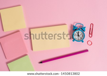 Four multicolor blank notepads message rubber band marker pen small alarm clock wakeup clip colored background empty text important events home office school
