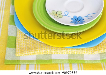 Four multicolored plates with napkins, same colors