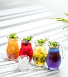 Four multicolored refreshing lemonades with ice. Minimal decor and sunshine.