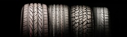 four new car tires in a row for passenger cars and crossovers. for different seasons, for autumn, summer, and mud all-season. long panorama layout